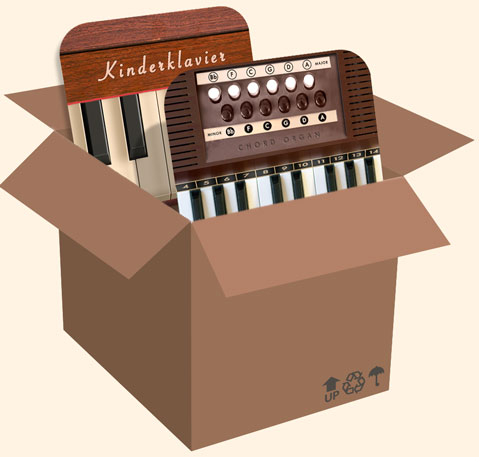 Chord Organ and Kinderklavier sitting comfortably inside a cardboard box